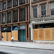 Nike and Lucky Brans Jeans stores board up windows in preparation for another expected night of protests due to the killing of George Floyd by a Minnesota Police Officer on Tuesday, June 2, 2020 in Manhattan, New York.  A citywide 8 p.m. curfew was ordered by NY Mayor Bill de Blasio amid the Floyd protests. (Alex Menendez via AP)