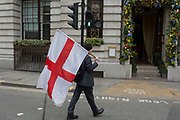 A patriotic man carries the English flag on St Georges Day the the streets of the capitals financial district aka The Square Mile, on 23rd April, City of London, England.