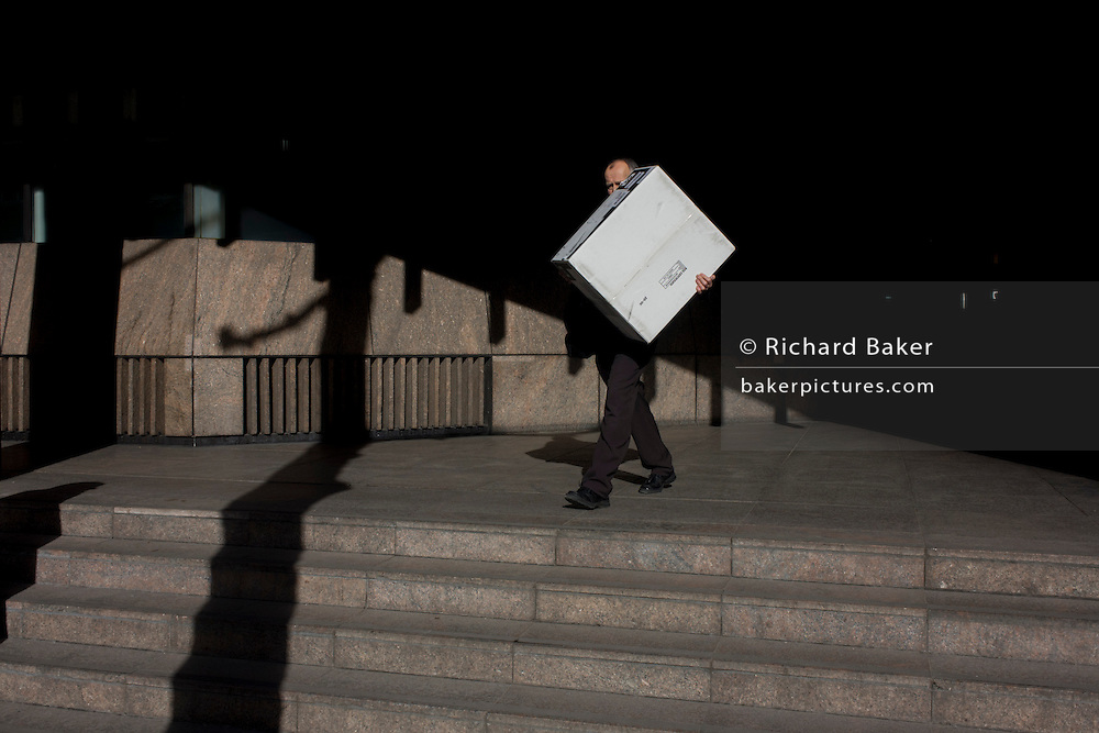 A man carrying a white box emerges from shadows in the Broadgate development in the City of London.