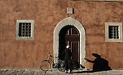 Priest with bicycle unlocks a door in Pisa, Italy.