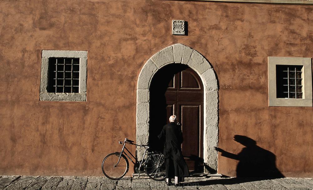 Priest with bicycle unlocks a door in Pisa, Italy.
