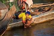 FISHERMEN MEKONG RIVER. South East Asia, Cambodia, Phnom Penh, Mekong River. The Cham fisher people live in various desolated villages along the banks of the Mekong and Tonle Sap rivers. The fisher families live like river gypsy nomads, working and living on their boats, sleeping under a sprung bamboo frame, all their worldly goods stored below deck. They live in extended families, with numerous boats, together for safety. Their diet is rice, vegetables and fish. Their sleek wooden boats are powered by petrol outboard motors with batteries or generators to supply lighting at night. Their fishing technique is laying nets twice or three times per day, which are weighted well below the surface, using old paint aerosal canisters as buoyant floaters, hanging just beneath the surface. These particular fisher families, living at the junction of the Mekong and Tonle Sap rivers, overlooked by Phnom Penh, sell their catch at the Vietnamese market, on the banks of the river. Their life and fortunes are controlled by the cycle of the river. As the river levels drop, so the quantity of fish decreases, until after the heavy floods of the monsoon they fill the river again. They are poor traditional Muslims, marginalised from mainstream society, living a third world life in the immmediate shadow of the first world. The Cham, originally a people of an ancient kingdom called Champa, are a small and disenfranchised community who were disinherited of their land. They are a socially important ethnic group in Cambodia, numbering close to 300,000. The Cham people, live in some 400 villages across Kampong Chnang and Kampong Cham provinces. Their religion is Muslim and their language belongs to the Malayo-Polynesian family. Their livelihoods are as diverse as rice farming, cattle trading, hunting and fishing.///Cham women washes her baby in the Mekong river