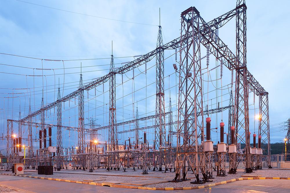 Illuminated electricity substation at dusk.