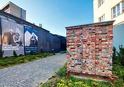 """Kraków, 2018-08-29. MOCAK postindustrialne muzeum sztuki współczesnej MOCAK działające na terenie dawnej Fabryki Schindlera.  Fragment muru to """"Dar Gdańska dla Krakowa"""" autorstwa Doroty Nieznalskiej. Został zbudowany z cegieł pozostałych po rozbiórce jednej z hal znajdujących się na terenie stoczni. Zabłocie. - zaniedbana do niedawna prawobrzeżna dzielnica Krakowa, aktualnie jeden z najbardziej dynamicznie rozwijających się obszarów Krakowa. Rewitalizacja i rosnący prestiż tego miejsca, powoduje, że Zabłocie stało się atrakcyjnym terenem dla deweloperów, inwestorów, mieszkańców jak również dla ludzi kultury i sztuki.Powstają tu modne restauracje i puby a mieszkańcy Krakowa coraz częściej wybierają Zabłocie jako miejsce zamieszkania i wypoczynku zamiast ciasnego Starego Miasta i Kazimierza."""