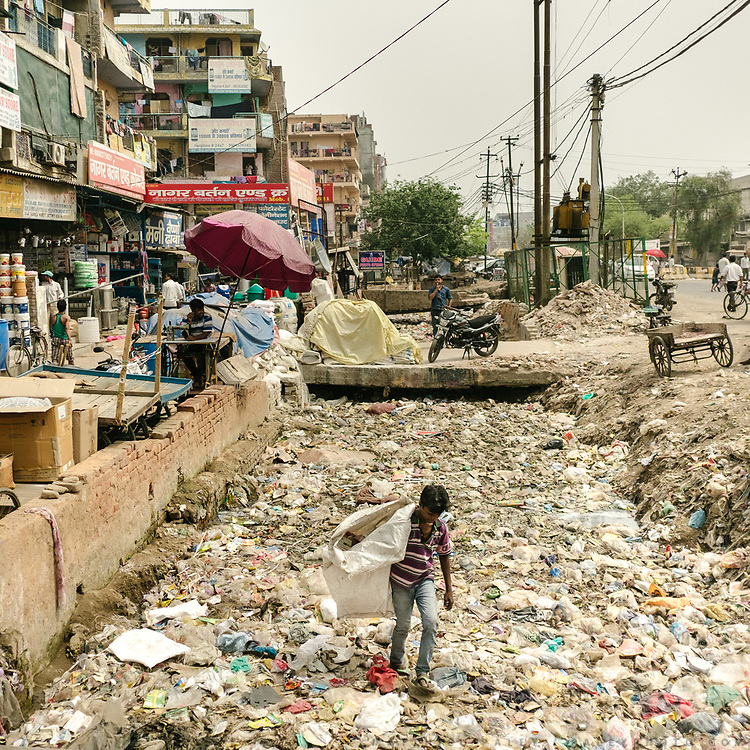 A sewage drain, so filled with years of garbages that one can actually walk on top of it. A boy goes to look for plastic and paper. Area inhabited by recyclers (Kabari) in Noida (around sector 16), on the border with Delhi.