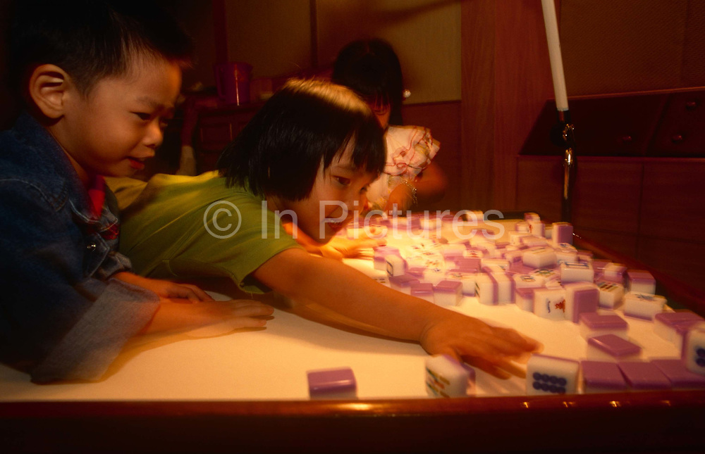 Children play with Mahjong tiles at a night-club, on 10th August 1994, in Macau, China. The Macau Special Administrative Region is one of the two special administrative regions of the Peoples Republic of China PRC, along with Hong Kong. Administered by Portugal until 1999, it was the oldest European colony in China, dating back to the 16th century. The administrative power over Macau was transferred to the Peoples Republic of China PRC in 1999, 2 years after Hong Kongs own handover.
