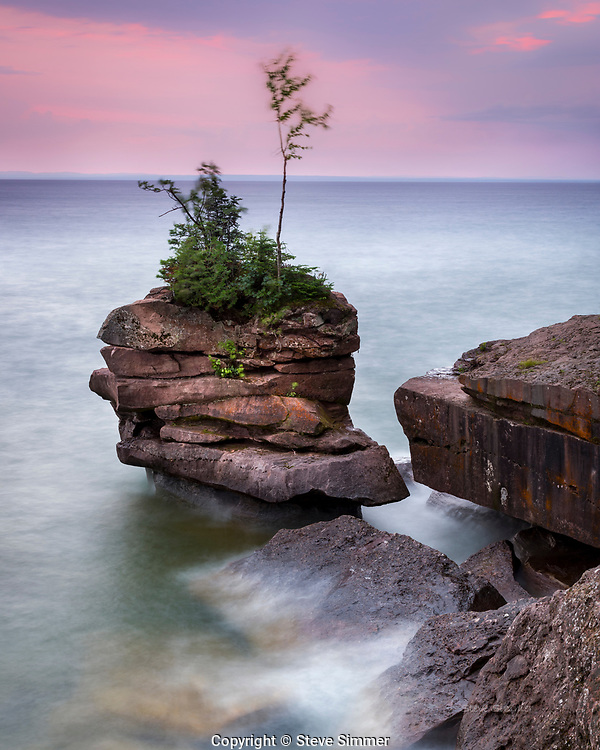 Before sunrise. Too cloudy to see the sun and light enough to show some color.  Wind from an approaching low pressure system was creating wave. This long exposure shows that the only thing not moving is the rock.