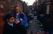 "Surrounded by black bin-bags during the Merseyside dustmans' strike of 1991, two young ""Scouse' girls lean against a brick wall in a rear alleyway between poor terraced housing in Liverpool, England. There is an older, taller white teenage girl with blonde hair dressed in a blue shell-suit and a shorter and younger friend of Asian-descent. Looking suspicious and amused at something across the cobbled alley of these 'back to back' houses in a poor area, South of the city centre, home to deprived families. The industrial action aginst the local authority was a health problem for Liverpool during the summer of '91 when streets filled with rubbish. Vermin like rats ran around and public city parks filled with every kind of refuse and garbage. Few of these back-to-backs exist after being cleared to allow construction of high-rise tower-blocks and flats."