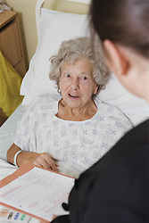 Elderly woman lying in hospital bed on ENT ward talking to Operational services manager looking anxious,