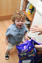 Toddler having a temper tantrum after being refused a packet of crisps,