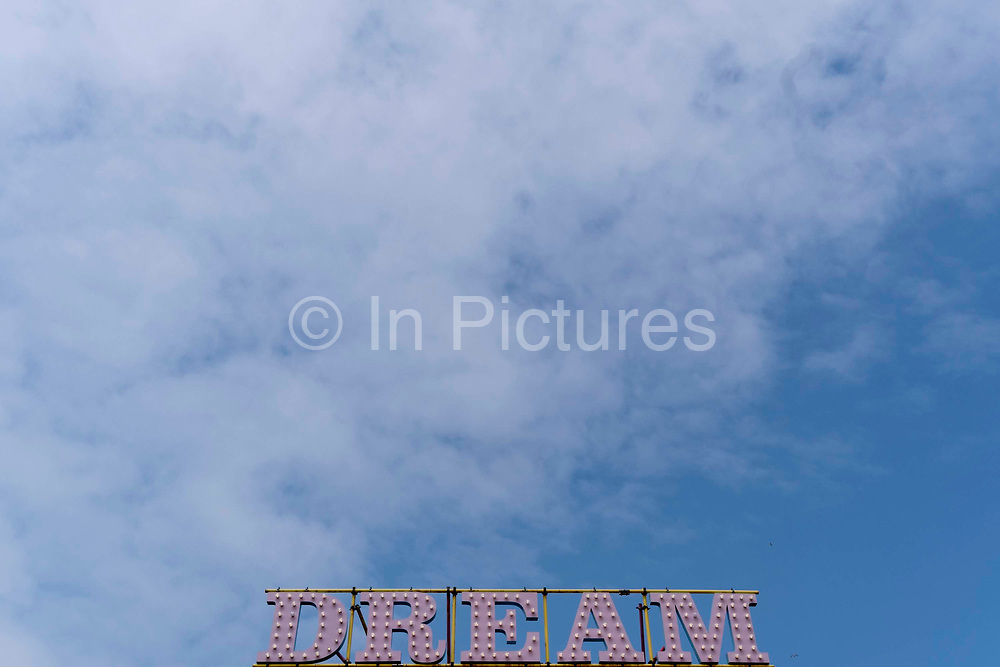 The word Dream is beneath a blue sky and high cloud, at Dreamland, the historical funfair in the English seaside town of Margate, on 26th July, in Margate, Kent, England.
