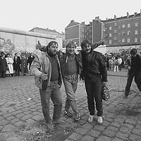 Junge Männer aus der DDR, die soeben zu Fuß zum ersten Mal in ihrem Leben über die offene Grenze von Ost- nach Westberlin gekommen sind und sich ihrem Freuden- und Alkoholtaumel hingeben. Sie freuen sich sichtlich, daß sich ein Fotograf für ihre Stimmung interessiert. Im Hintergrund viele Bewohner der DDR, die sich für ihren ersten Ausflug in den Westen besonders fein gemacht haben.