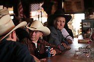 Two very young cowboys and one old one sitting at the Bluedog Saloon. This is west of Tucson near a place called Three Points or Robles Junction. The older cowboy is Roos Loney who was a fearless rodeo bronc rider.