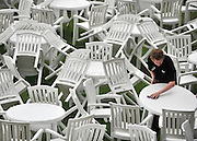 © licensed to London News Pictures. ASCOT, UK.  16/06/11. A member of staff drys tables and chairs after a heavy downpour. Ladies Day at Royal Ascot 16 June 2011. Royal Ascot has established itself as a national institution and the centrepiece of the British social calendar as well as being a stage for the best racehorses in the world. Mandatory Credit Stephen Simpson/LNP