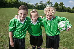 Three young soccer players posing portrait happy