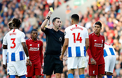 """Match referee Chris Kavanagh shows a yellow card to Brighton & Hove Albion's Leon Balogun during the Premier League match at Anfield, Liverpool. PRESS ASSOCIATION Photo. Picture date: Saturday August 25, 2018. See PA story SOCCER Liverpool. Photo credit should read: Martin Rickett/PA Wire. RESTRICTIONS: EDITORIAL USE ONLY No use with unauthorised audio, video, data, fixture lists, club/league logos or """"live"""" services. Online in-match use limited to 120 images, no video emulation. No use in betting, games or single club/league/player publications."""