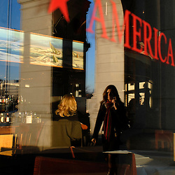 WASHINGTON, DC -- A commuter talking on her cell phone in the outdoor promenade of Union Station is reflected in the window of restaurant, America, where late-afternoon diners sit at the bar....Photo by Susana Raab