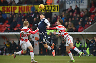 Lee Gregory of Millwall FC heads ball clear of Craig Alcock of Doncaster Rovers of Doncaster Rovers and Mitchell Lund of Doncaster Rovers during the Sky Bet League 1 match between Doncaster Rovers and Millwall at the Keepmoat Stadium, Doncaster, England on 27 February 2016. Photo by Ian Lyall.