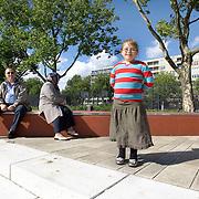 Nederland Rotterdam 20 juli 2008 20080720 Foto: David Rozing .Serie achterstandswijk Afrikaanderwijk. Allochtoon meisje poseert op Afrikaanderplein, op achtergrond haar vader en moeder...Foto David Rozing
