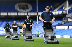 Everton groundsmen trim the grass after the game