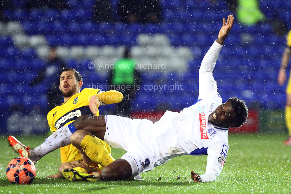 Jake Wright of Oxford United tackles Kayode Odejayi of Tranmere Rovers (r). The FA Cup, 2nd round replay, Tranmere Rovers v Oxford United at Prenton Park in Birkenhead, England on Tuesday 16th December 2014.<br /> pic by Chris Stading, Andrew Orchard sports photography.