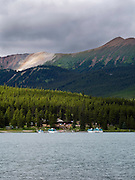 View of the lodge and tour boats on the north shore of Maligne Lake on an overcast day; Jasper National Park, Alberta, Canada