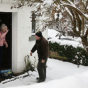 Gordon Anderson delivers fresh milk and vegetables to a local resident shielding from Covid-19 and the snow, 14th of January 2021, Scotland, United Kingdom. Gordon Anderson runs a fresh milk and vegetables delivery service with his wife and they deliver to local houses and farms in and around the village of Stow. The first real snow of the year has been falling all night and morning and the village is covered in fresh snow.