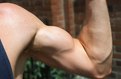 Body builder showing off biceps muscle by flexing his arm,