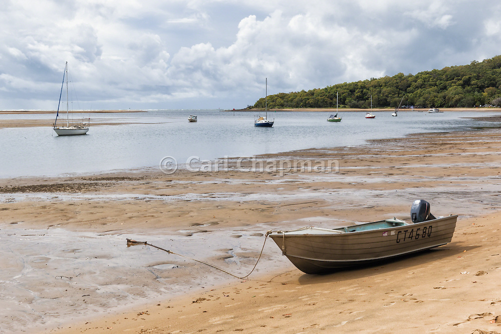 Tinnie dinghy on beach shore at low tide with sailboats in 1770 Seventeen Seventy, Queensland, Australia <br />