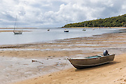 Tinnie dinghy on beach shore at low tide with sailboats in 1770 Seventeen Seventy, Queensland, Australia <br /> <br /> Editions:- Open Edition Print / Stock Image