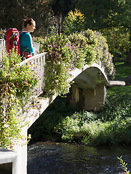 Woman on hiking tour in the Northern Black Forest, crossing bridge near Bad Liebenzell, Baden-Württemberg, Germany