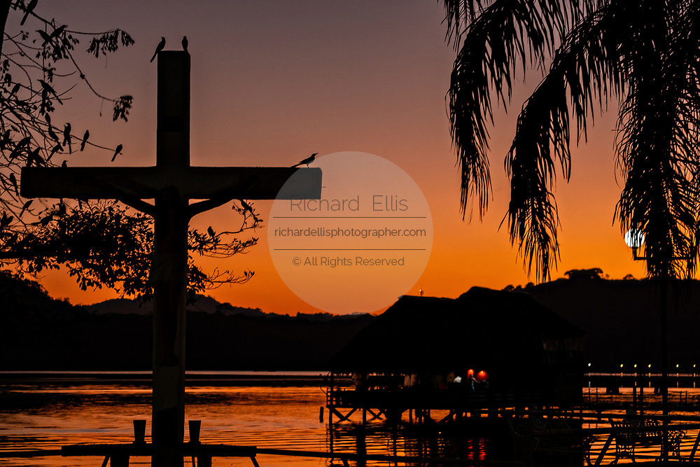 Sunset over Lake Catemaco in Catemaco, Veracruz, Mexico. The tropical freshwater lake at the center of the Sierra de Los Tuxtlas, is a popular tourist destination and known for free ranging monkeys, the rainforest backdrop and Mexican witches known as Brujos.