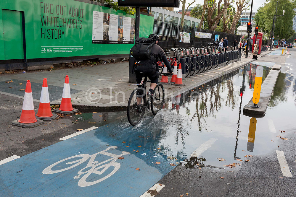 A cyclist rides through collected water on a section of the CS2 cycling superhighway after recent rainfall, on 29th August 2018, in London, England. The CS2 cycle route is about 4.3 miles 6.8 kilometres, from Stratford to Aldgate.