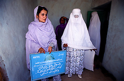 YAFTAL PAYAN, 31 July 2005..Women standing at the entrance of Bitha Bala's Vocational Training Centre.  ....The VTC aim is to improve the status of women, by giving them lessons on maternity, family planning and post-natal issues. ....According to United Nations Population Fund, Afghanistan has among the world?s highest rates of maternal mortality, and Badakhshan has the highest rates ever recorded anywhere in the world, with one mother dying in every 15 births. Underage marriage is one of the primary causes of maternal mortality.....The VTC is funded by UNFPA and implemented by IBNSINA.