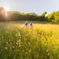 A couple walks in a hay field in Jackson, New Hampshire. White Mountains.