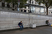 A man uses his laptop beneath the slogan 'Live Simply and Live in Peace' has been written on a wall by an environmental activist protesting about Climate Change during an occupation of Trafalgar Square in central London, the third day of a two-week prolonged worldwide protest by members of Extinction Rebellion, on 9th October 2019, in London, England.