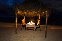 A honeymooning couple enjoy a private dinner on the beach, Vatulele Island Resort, Fiji Islands