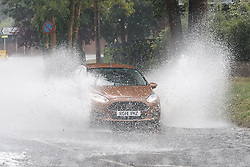 © Licensed to London News Pictures. 13/08/2020. Leatherhead, UK. Cars drive through floodwater as the UK experiences thunderstorms and heavy rainfall following days of high temperatures. Photo credit: Peter Macdiarmid/LNP