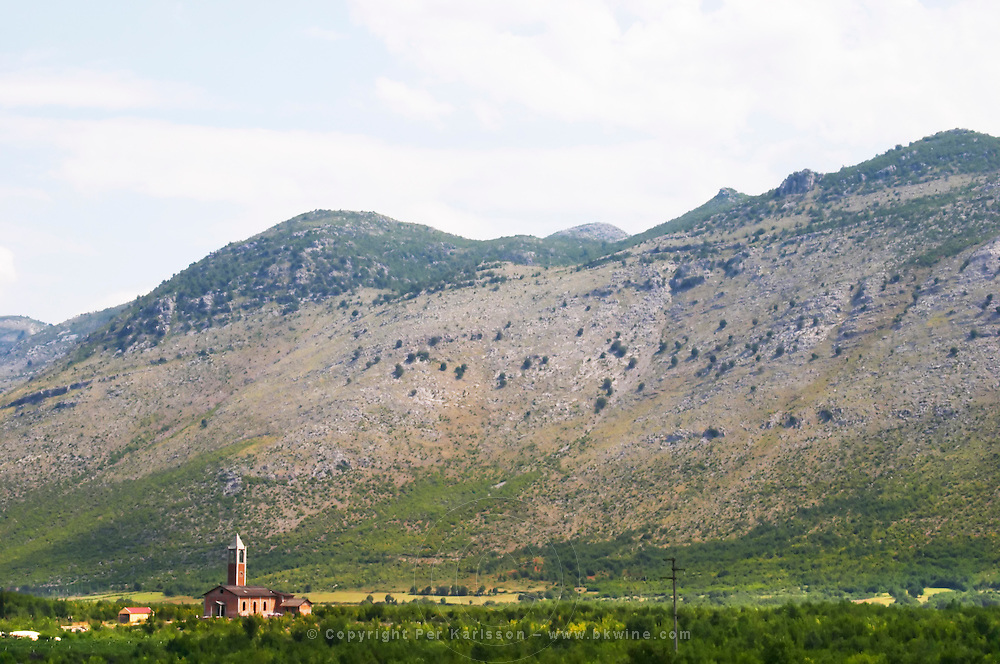 A church on the plain dominated by the Kastrat Shkrel mountains near Koplik and the Montenegro border. Albania, Balkan, Europe.