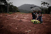 People leave flowers after a burial of a landslide victim in Teresopolis, Brazil, Friday, Jan. 14, 2011. <br /> <br /> A series of flash floods and mudslides struck several cities in Rio de Janeiro State, destroying houses, roads and more. More than 900 people are reported to have been killed and over 300 remain missing in this, Brazil's worst-ever natural disaster.