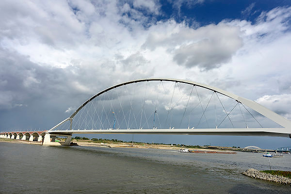 Nederland, Nijmegen, 11-9-2013Momenteel wordt de laatste hand gelegd aan de nieuwe stadsbrug van de stad Nijmegen, de Oversteek, genoemd naar de heldhaftige oversteek van de rivier de Waal die Amerikaanse soldaten op dit punt maakte tijdens de operatie Market Garden in de tweede wereldoorlog.De Oversteek is een boogbrug van 285 meter lang en 60 meter hoog en is de op een na langste hoofd overspanning van Nederland, en de grootste boogbrug van Europa met een enkelvoudige boog.De brug wordt in november in gebruik genomen.De nieuwe oeververbinding moet zorgen voor een betere spreiding en doorstroming van verkeer binnen de stad Nijmegen. Na 75 jaar is er eindelijk een tweede vaste verbinding voor de stad. De oude waalbrug krijgt vanaf eind dit jaar groot onderhoud, waarna de volle capaciteit van beide bruggen pas gebruikt kan worden. De skyline van de stad is voorgoed veranderd.Foto: Flip Franssen/Hollandse Hoogte