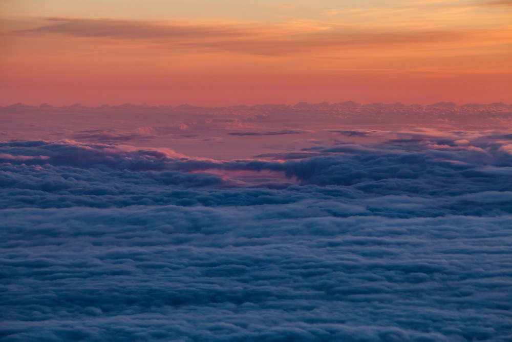 An aerial view far above clouds below at sunset.