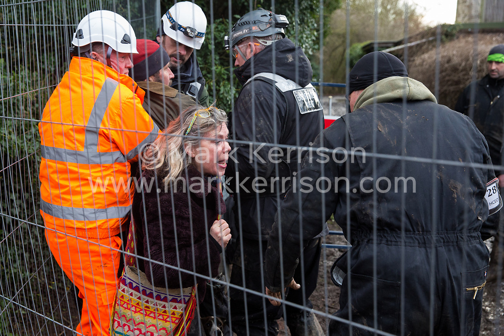 Harefield, UK. 16 January, 2020. Enforcement agents working on behalf of HS2 prevent Stop HS2 activist Mark Keir from reentering the Harvil Road wildlife protection camp in the Colne Valley after it was agreed that he could bring out dogs to a woman waiting outside belonging to a fellow activist evicted earlier in the morning from the camp after over two days and two nights spent in a tree in woodland.