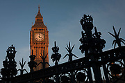 Silhouetted security railings featuring spikes and crowns and Elizabeth Tower of the British parliament, on 17th January 2017, in London England. The Elizabeth Tower previously called the Clock Tower named in tribute to Queen Elizabeth II in her Diamond Jubilee year – was raised as a part of Charles Barrys design for a new palace, after the old Palace of Westminster was largely destroyed by fire on the night of 16 October 1834. The new Parliament was built in a Neo-gothic style, completed in 1858 and is one of the most prominent symbols of both London and England.