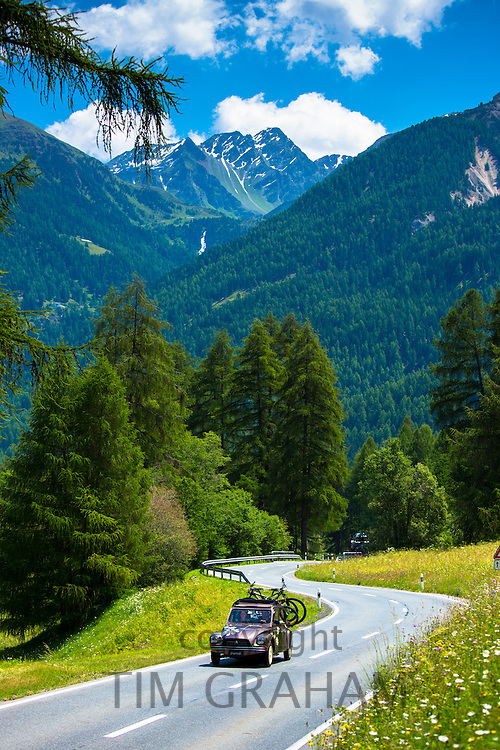 Citroen 2CV with bicycle rack on touring holiday in the Swiss Alps, Swiss National Park, Switzerland