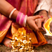 The bride and groom hold hands and feed the sacred fire during a Hindu wedding ceremony in New Delhi