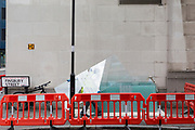 A contractor carries heavy and awkward sheets of glass from an office in Finsbury Street EC2, on 21st August 2018, in London, England.