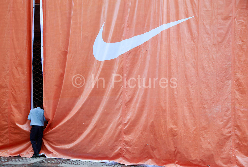 A guard peeks behind the construction drapes of a Nike store in Wenzhou, Zhejiang Province on 24 October, 2011. Wenzhou has seen a spate of business owners disappearing under the pressure of debt, as small and medium size businesses face increasing difficulties in securing loans, while the slow recovery of the European and U.S. economies continues to disappoint exporters.