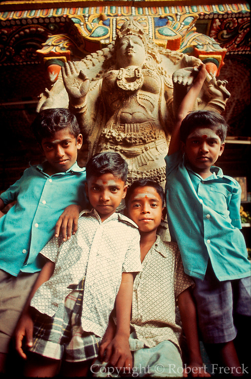 INDIA, RELIGION, HINDUISM Boys pose in front of a statue in the Meenakshi Temple in Madurai