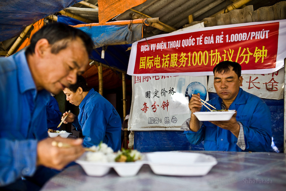 Chinese workers eat lunch with International phone call advertising in background, near the Haiphong Thermal Power Plant construction site in Trung Son, Vietnam, Nov. 22, 2009. At the construction site here, a few miles northeast of the port city of Haiphong, an entire Chinese world has sprung up, including four walled dormitory compounds for the Chinese workers, restaurants with Chinese signs advertising dumplings and fried rice, and currency exchange shops.